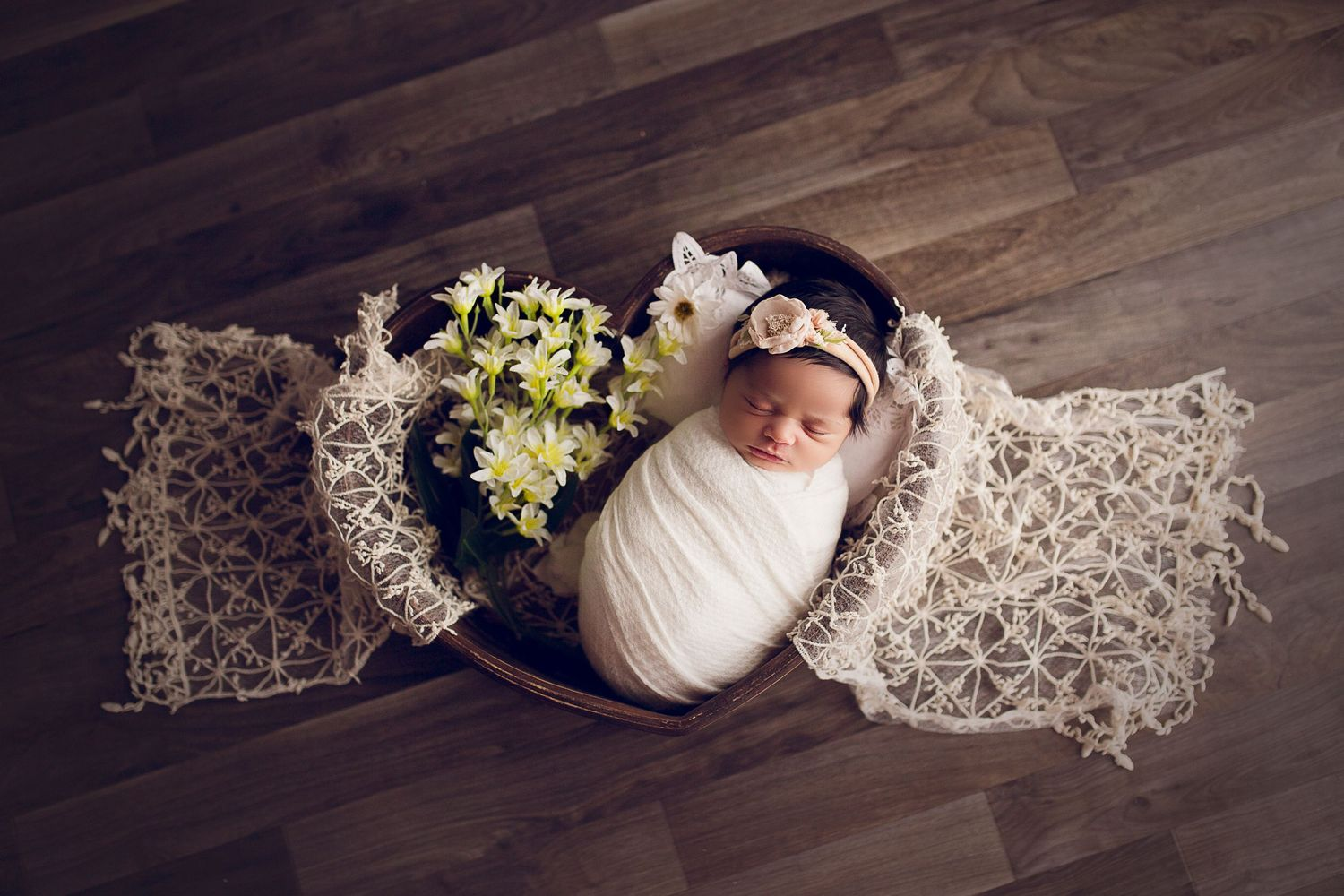 wrapped newborn girl in a wooden heart prop lace