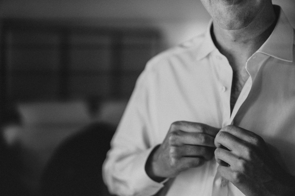 Groom buttons up his shirt as he gets ready for the wedding ceremony
