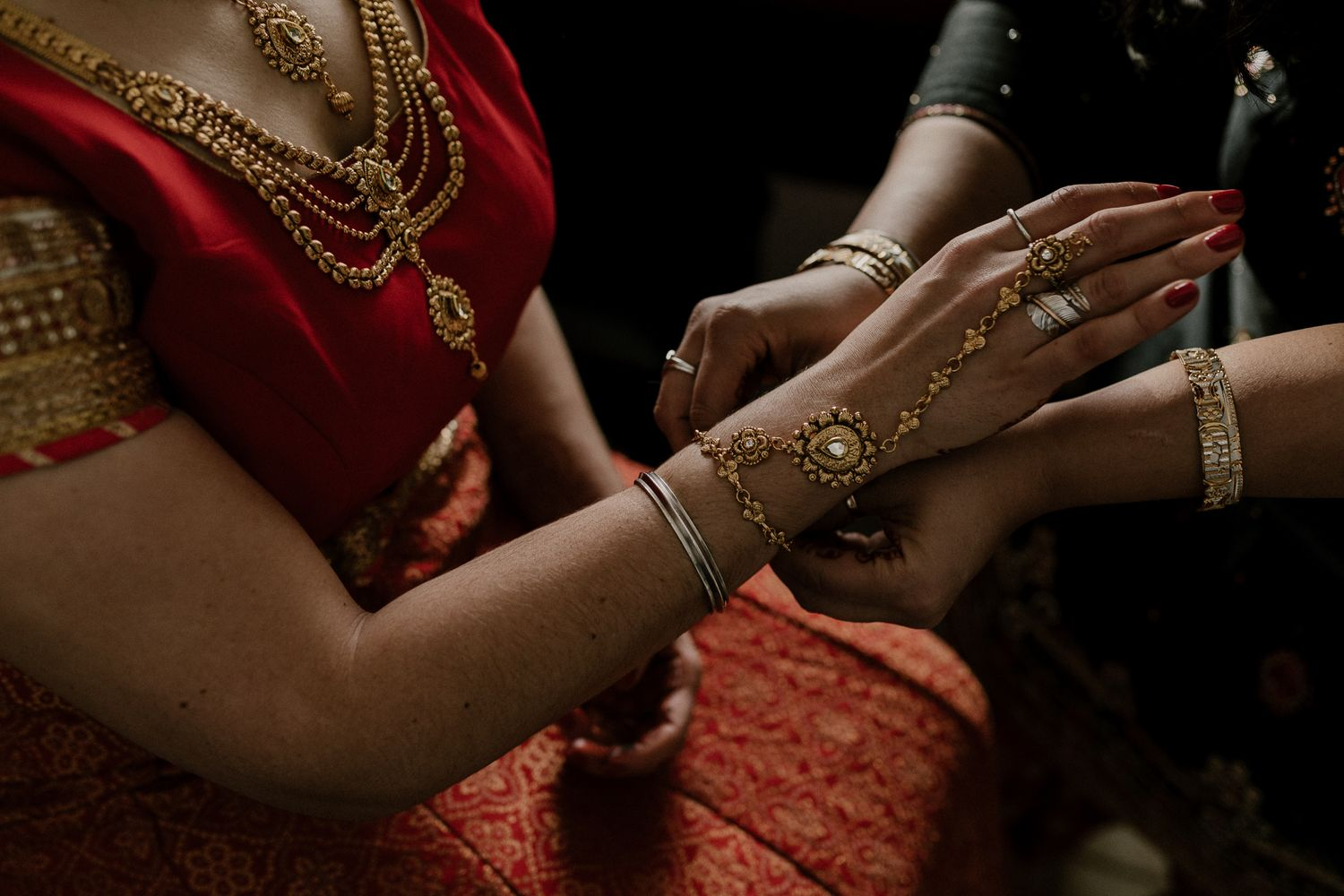 Toronto Sikh bride putting on her gold jewelry in red lehenga.