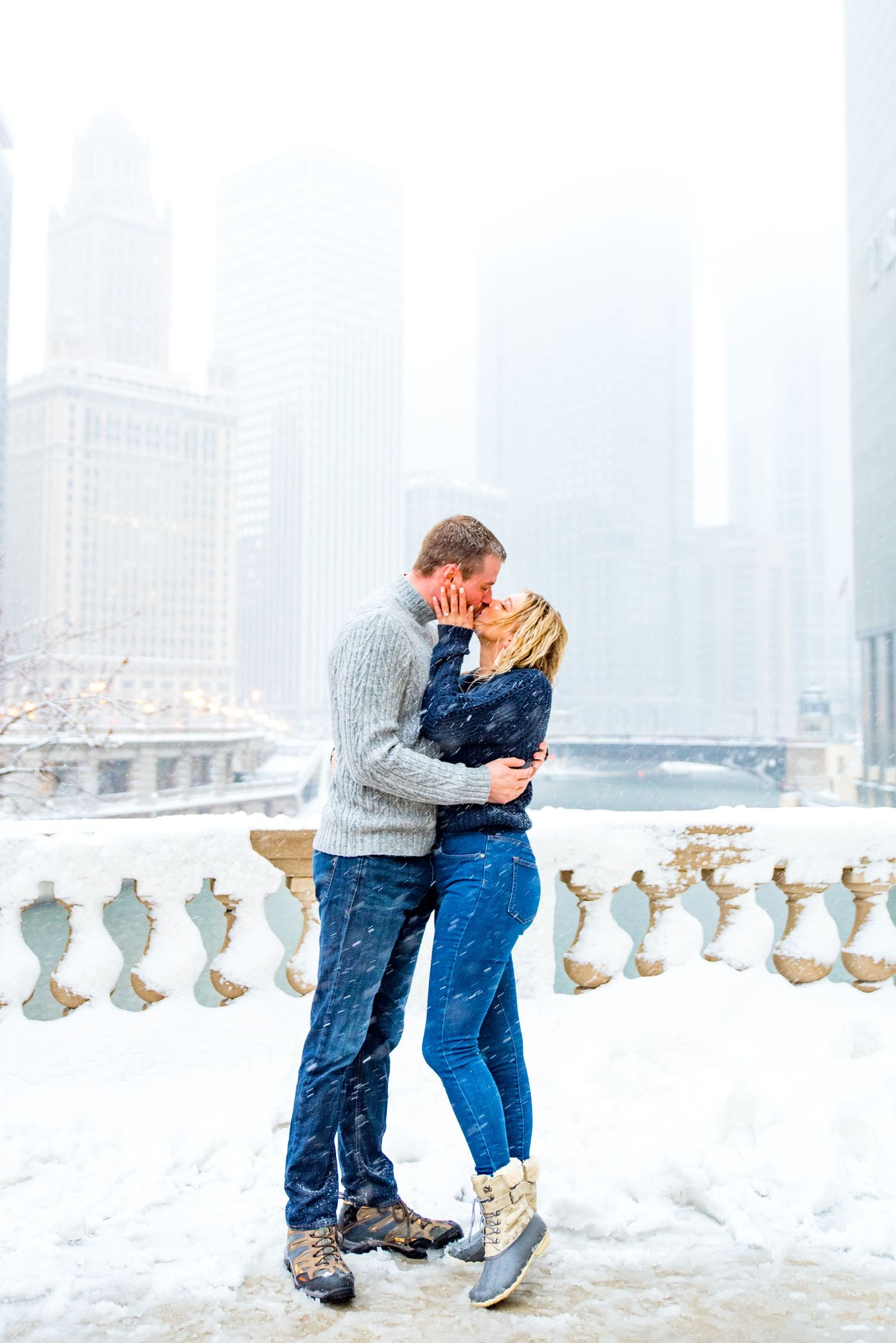 couple kissing in the snow at Wrigley Building overlooking the Chicago River for snowy winter engagement pictures