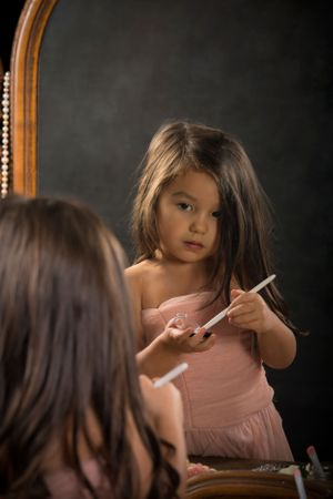 A little girl putting on makeup.