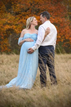 Long blue gown with a pregnant belly that the dad is holding.