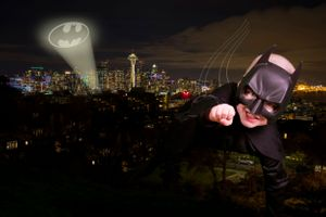 A boy dressed as batman flying over Seattle.