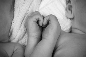 Twin newborn boys making a heart with their hands.