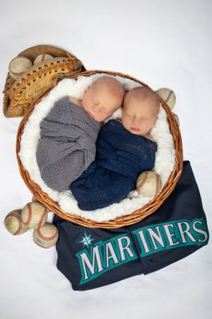 Twin newborn boys wrapped and placed in a basket over a Mariners jersey.