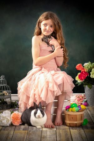A little girl in a peach dress holding a baby bunny.