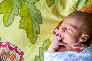 newborn with fingers in mouth