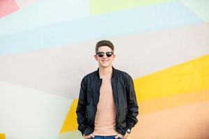 high school senior in front of bright wall with sunglasses