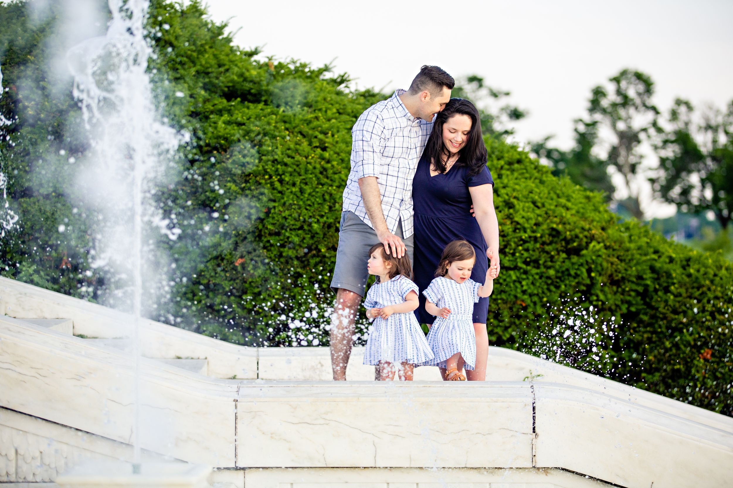 Family with twin girls standing by fountain