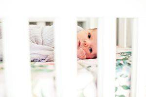 baby between crib slats