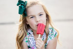 little girl licking red popsicle