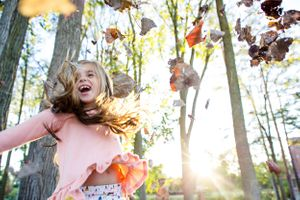 little girl twirling in fall with leaves