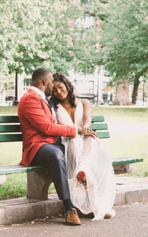 Boston couple sit on Boston common bench sharing a laugh for engagement photoshoot