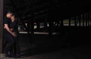 Couple under high school bleachers during Boston engagement photoshoot