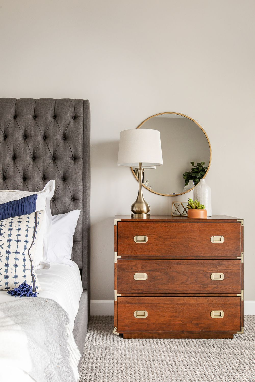 professional real estate photography - Bed with night stand, lamps and decor on the night stand with a mirror.