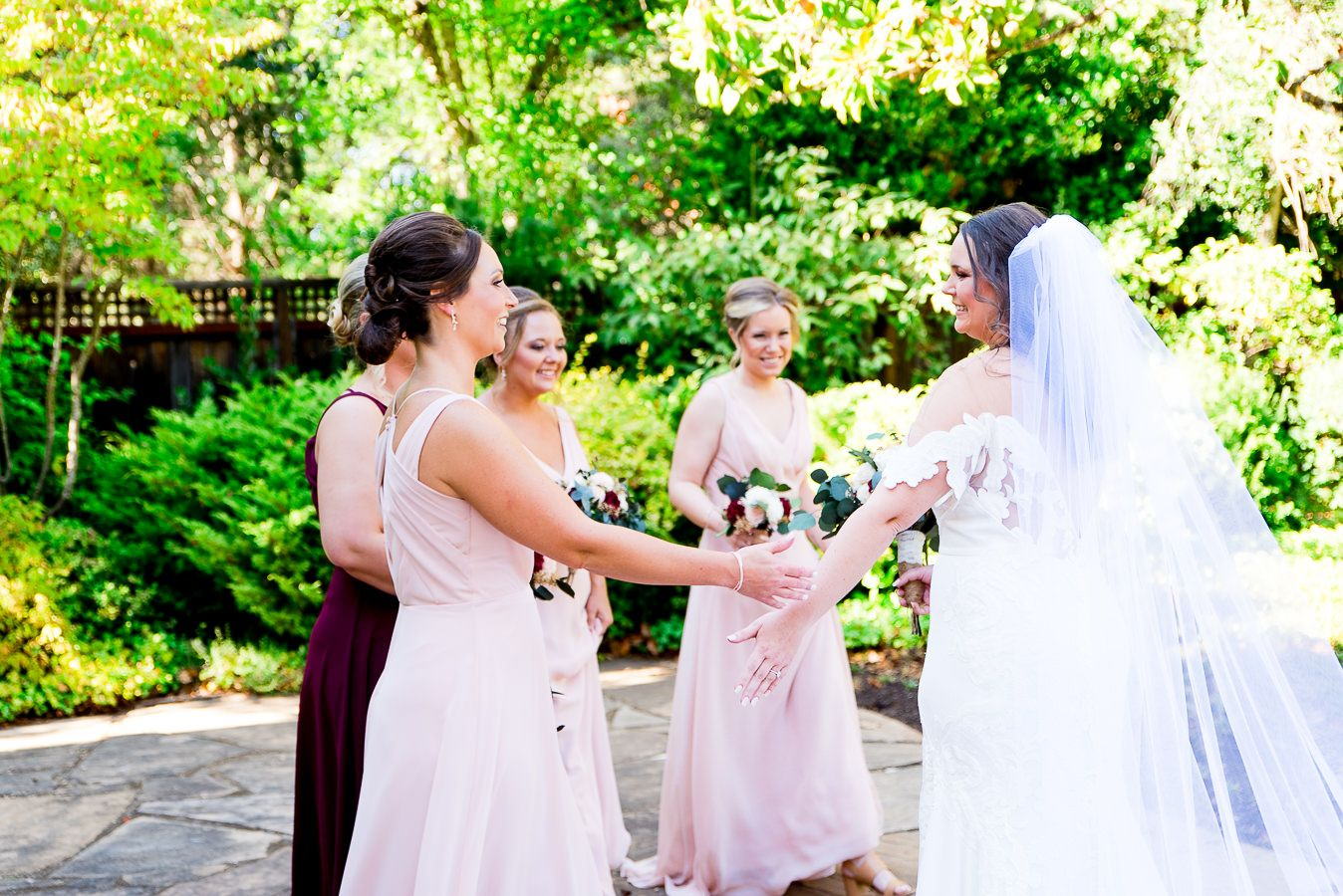 bridesmaids in blush and red hug the bride after they see her for the first time on wedding day
