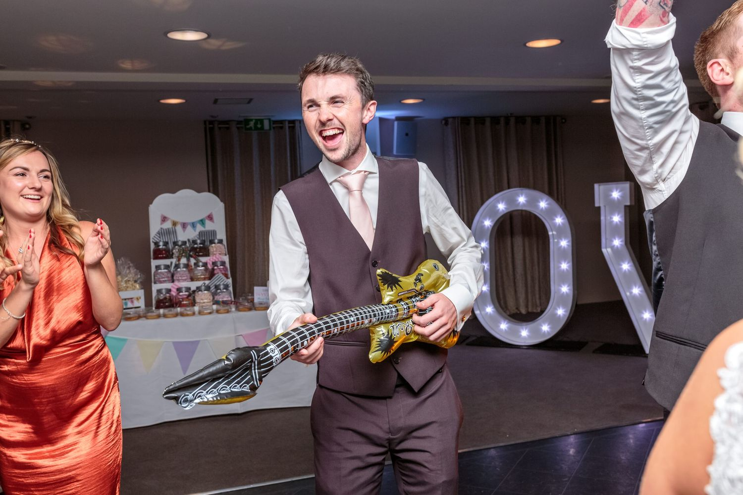 one of the wedding guests plays an inflatable guitar on the dance floor as the singing waiters entertain the guests