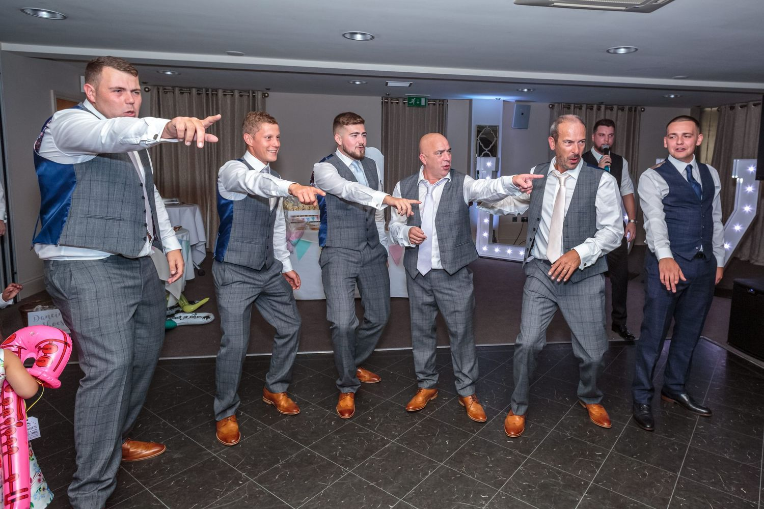 groomsmen lines up on the dancefloor pointing at the women during their impromptu dance routine