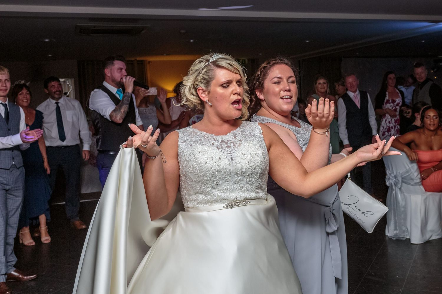bride and maid of honour dance back to back during the singing waiters performance