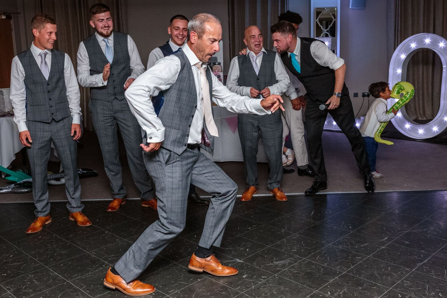 grooms father shows of his egyptian dance moves as the groomsmen watch on in the background