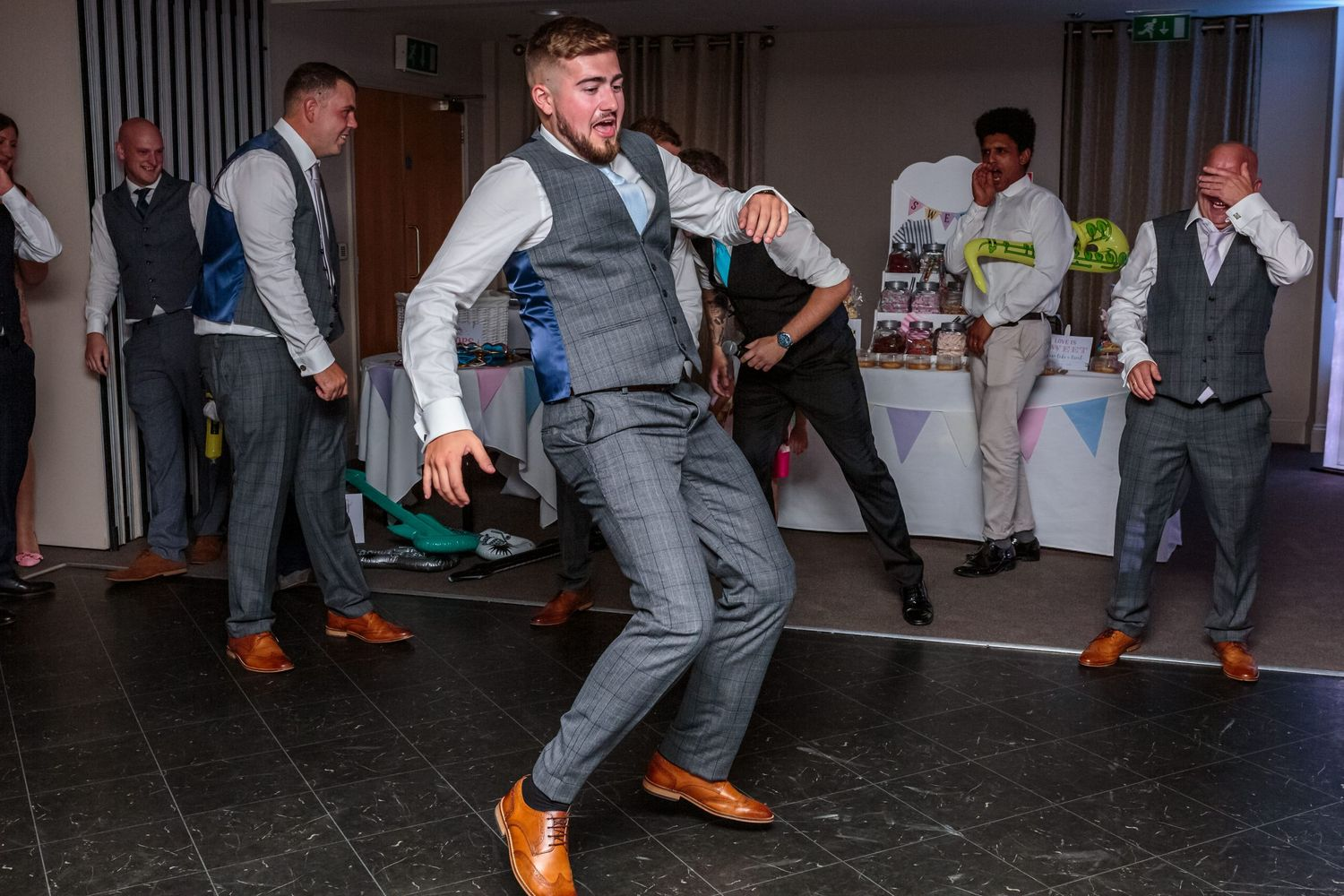 one of the groomsmen takes to the floor for his dance solo knees bent leaning back and arms outstretched