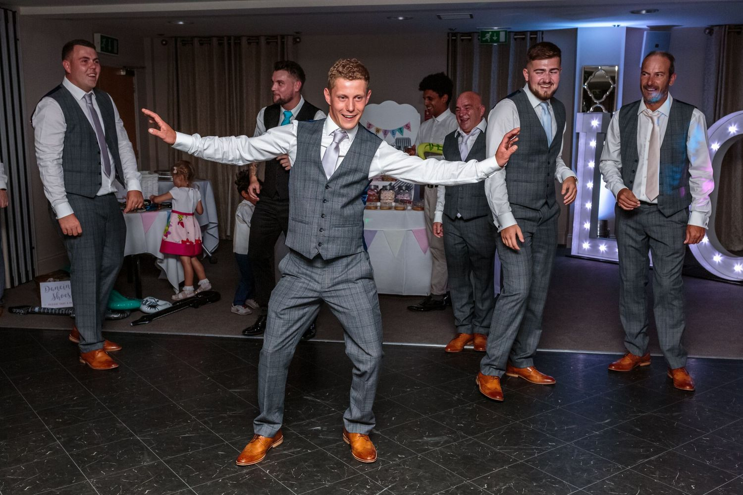 best man up for his dance solo arms outstretched as the rest of the groomsmen  watch on