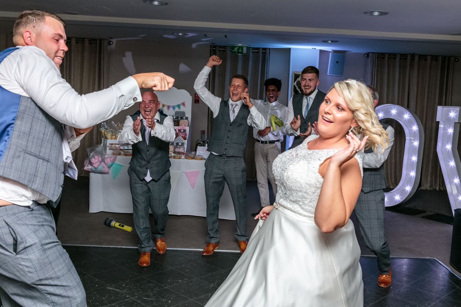 bride struggles as she is hooked by the groom during his dance solo as the groomsmen cheer in the background