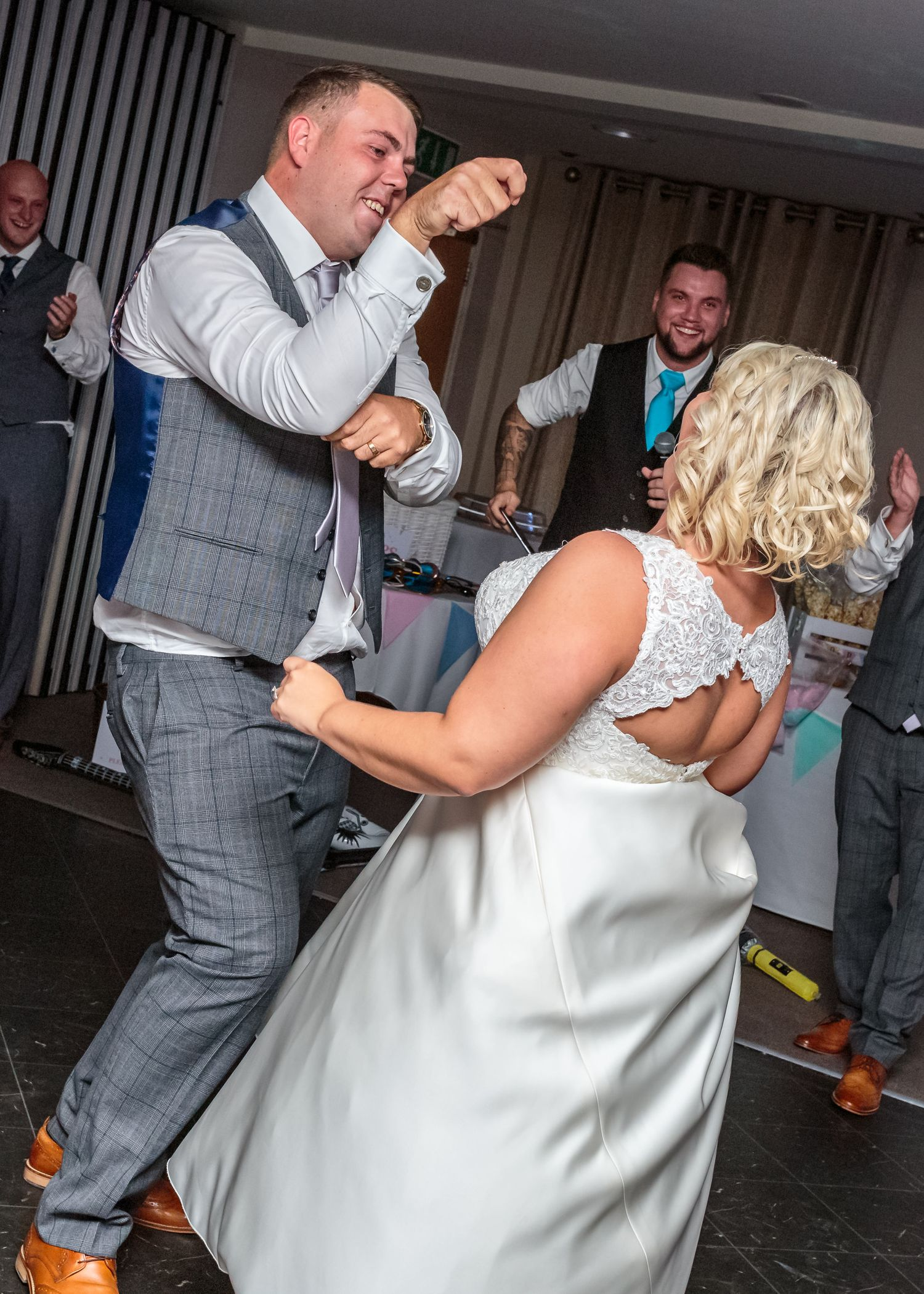 groom reels in his bride watched by the wedding guests surrounding the ribby hall dance floor
