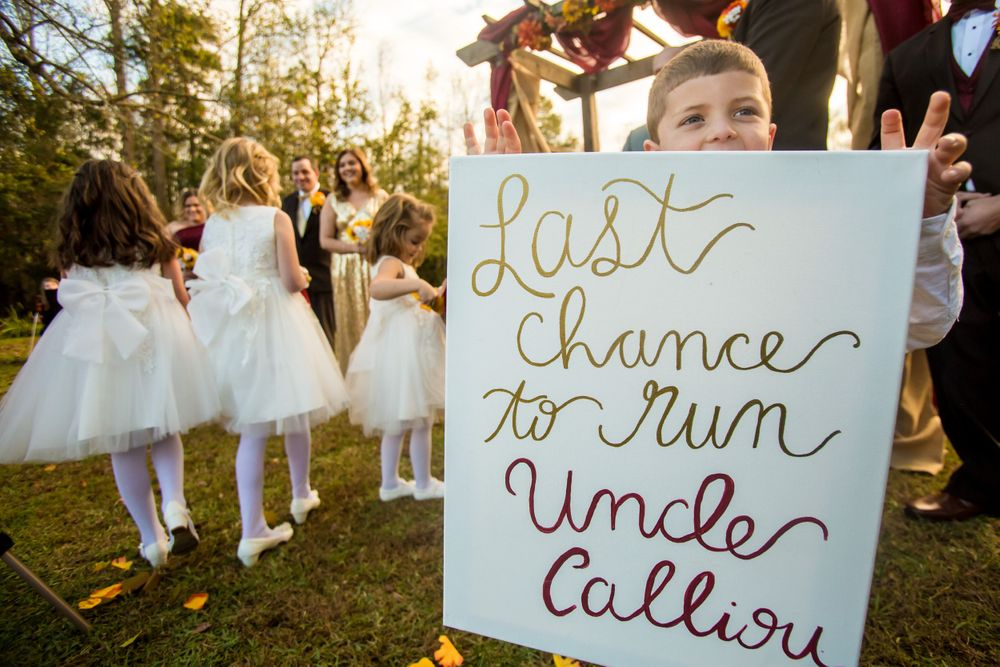"Ring bearers hold a ""Last Chance"" sign during a wedding at T&S Farm in Leesville, SC"