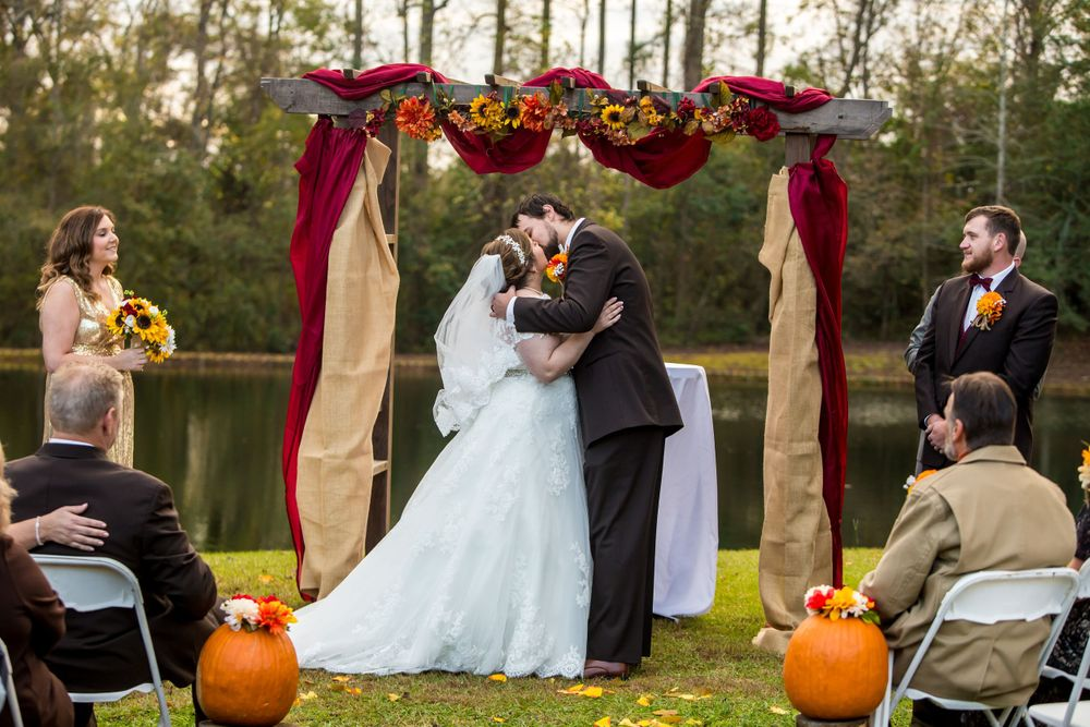 Bride Becca and groom Kyle have their first kiss during a wedding at T&S Farm in Leesville, SC