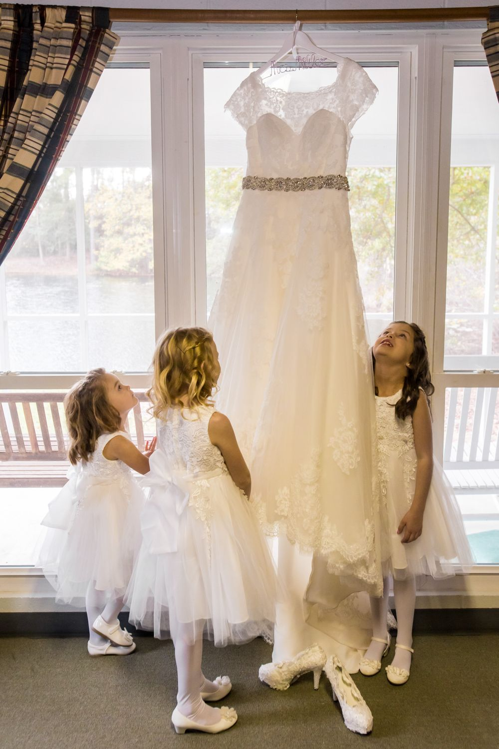 Flower girls inspect the bridal gown before during a wedding at T&S Farm in Leesville, SC