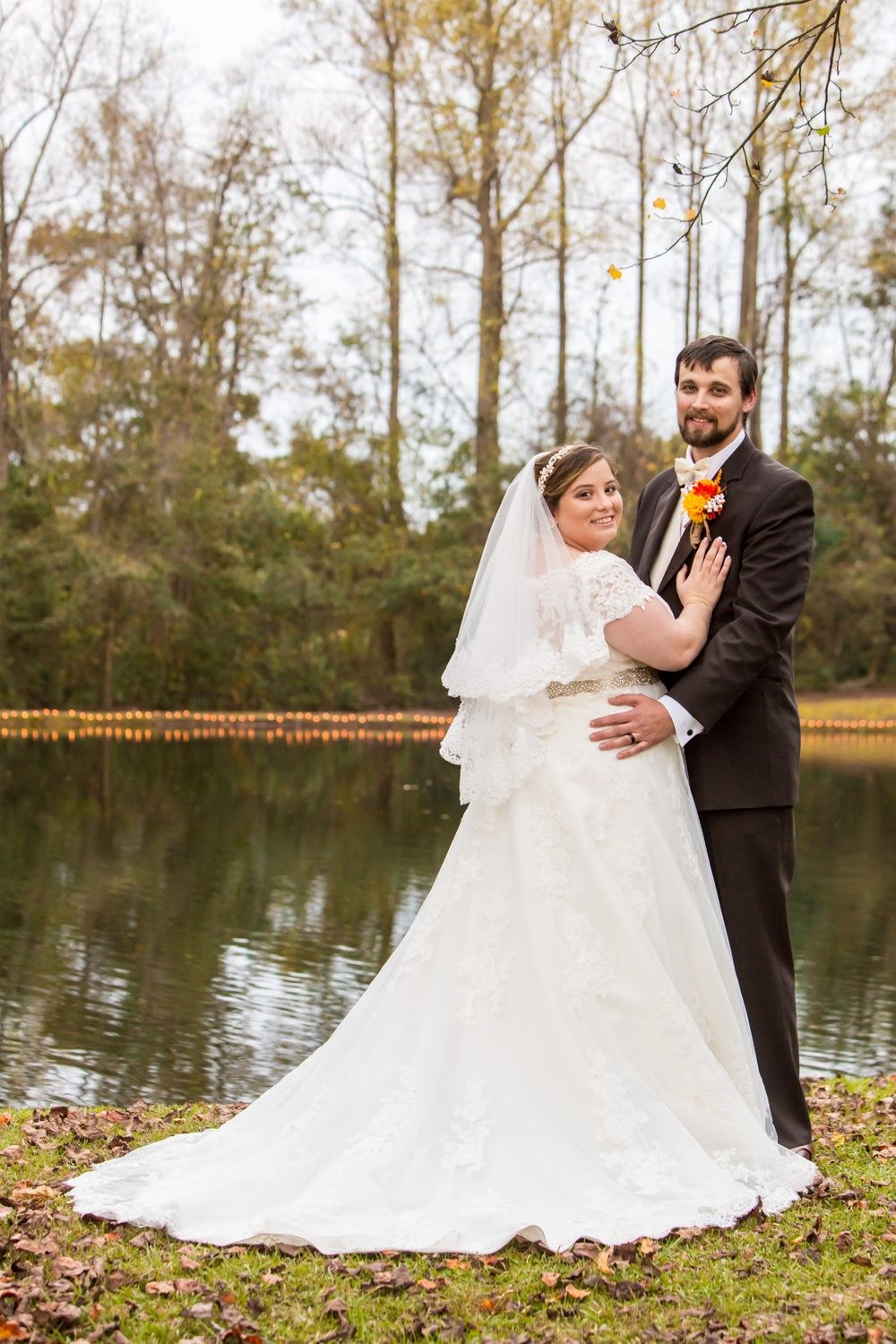 Bride Becca and groom Kyle pose by the pond after their wedding at T&S Farm in Leesville, SC