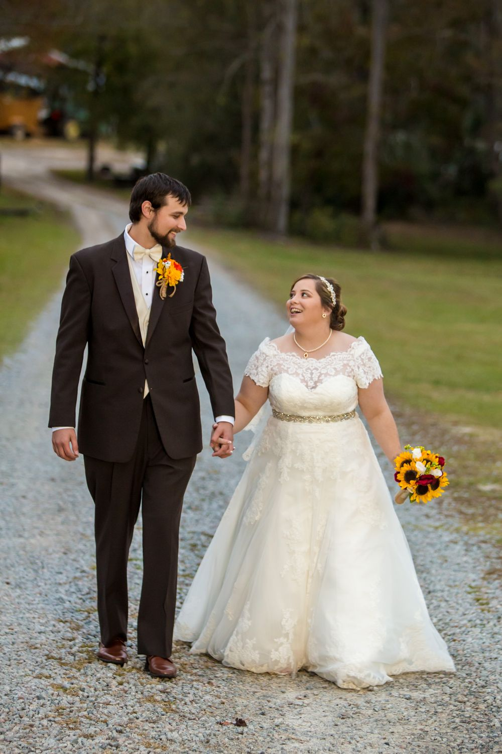 Becca and Kyle walk down a gravel road following their wedding at T&S Farm in Leesville, SC