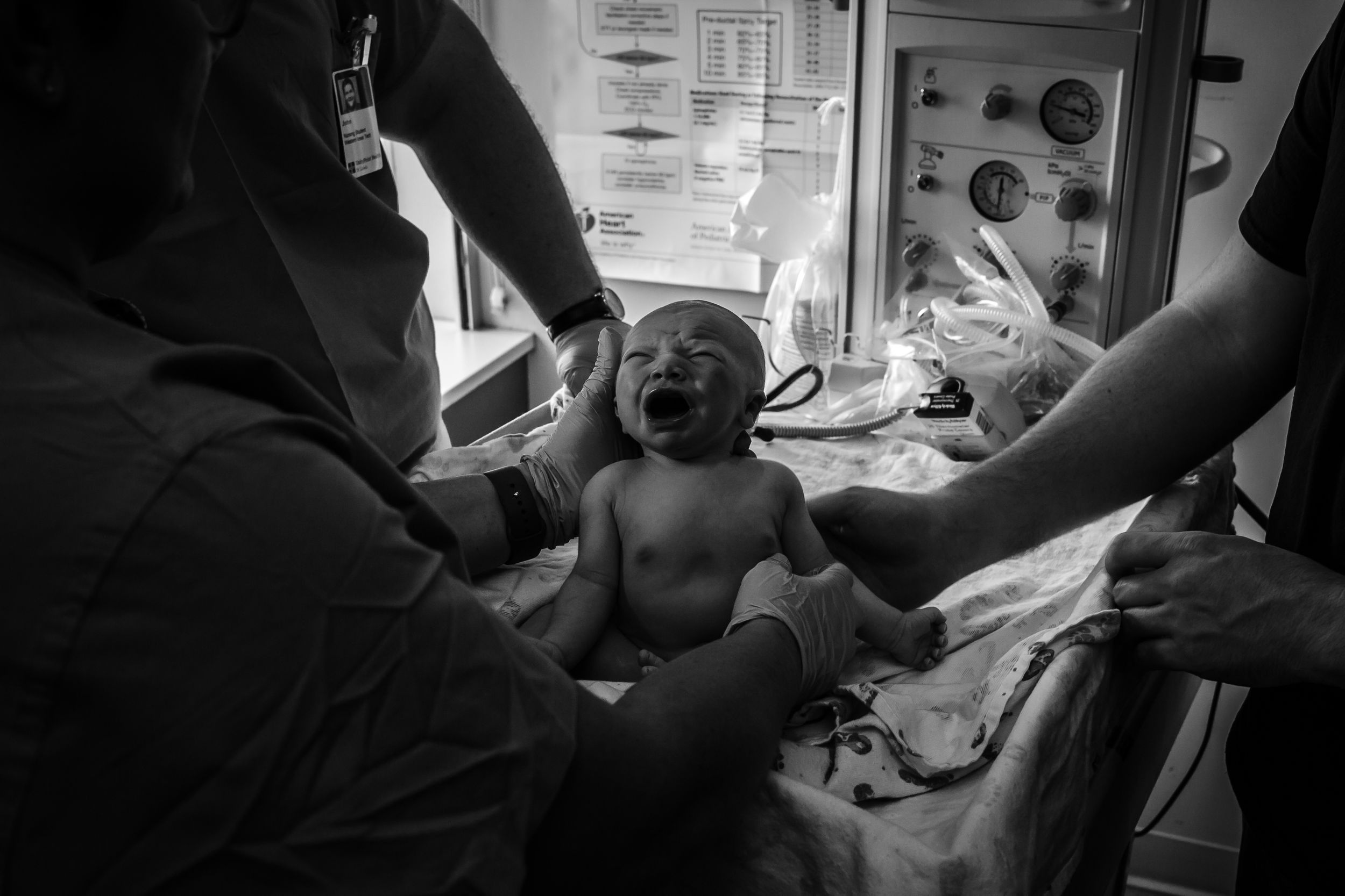 Newborn baby boy held up by a nurse and dad while getting his measurements done just after birth in Sioux City, IA.