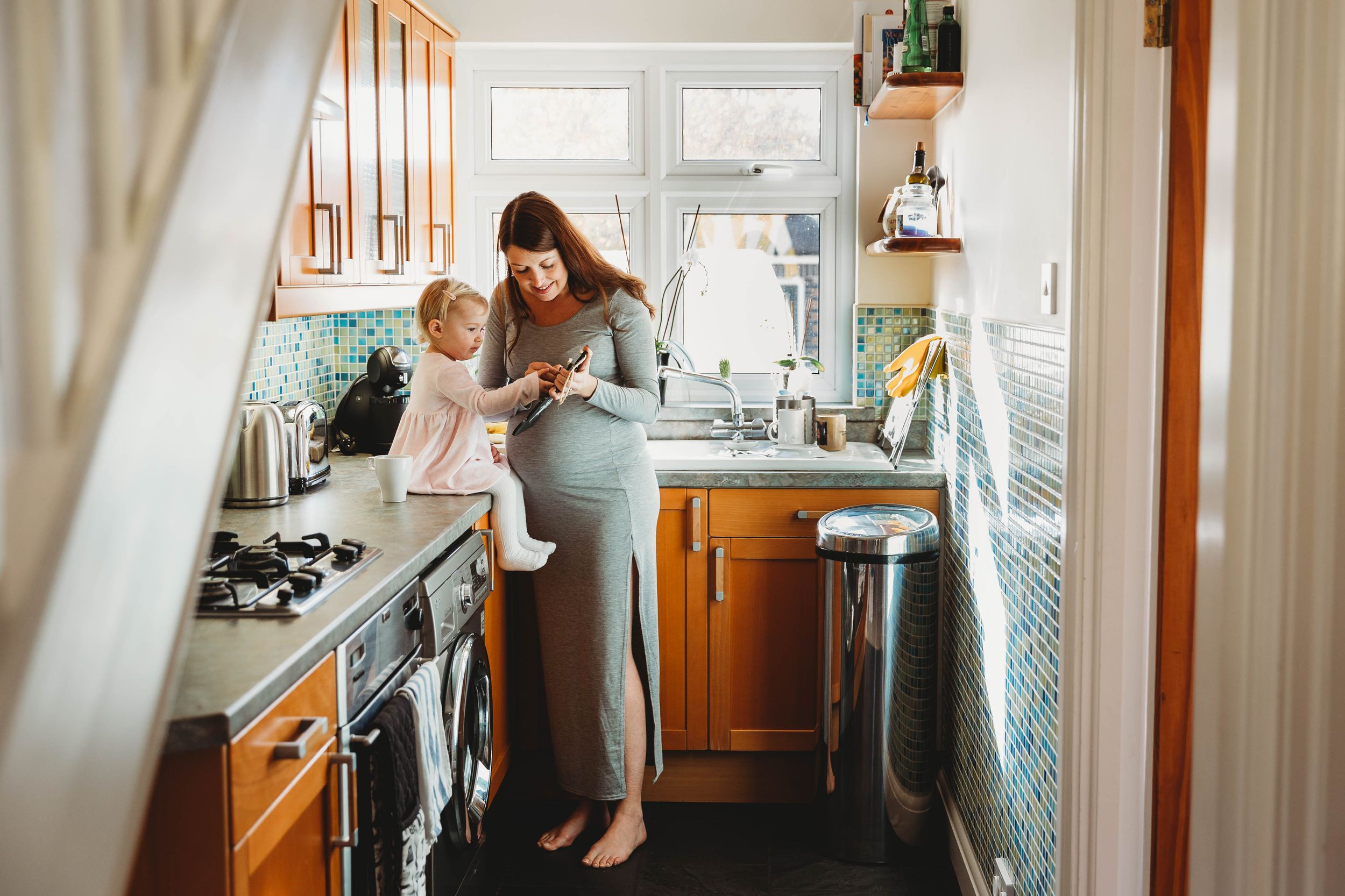 pregnant woman in grey maternity dress standing in kitchen with little girl