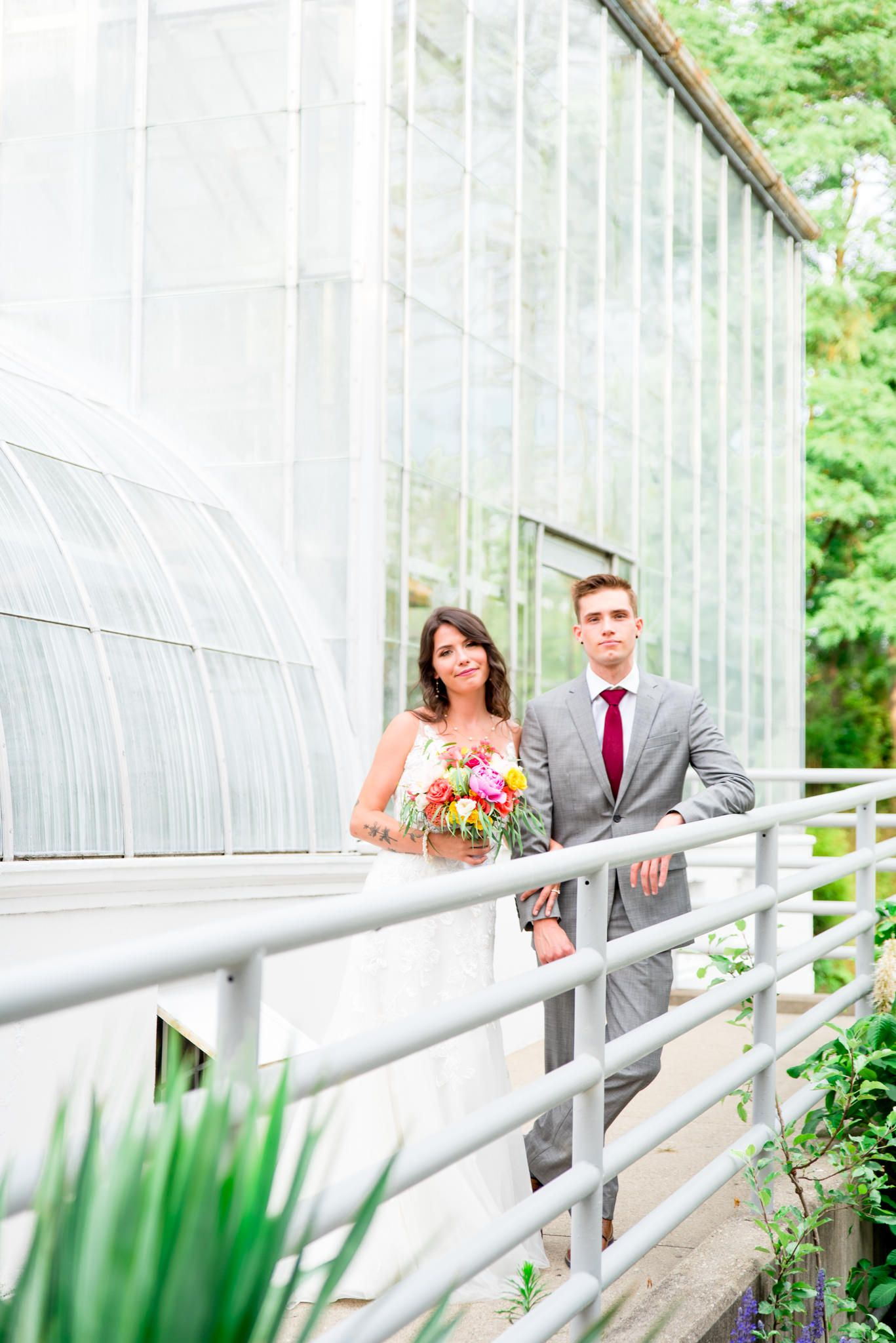 bride and groom stare into the camera in front of Krohn Conservatory for their summer wedding