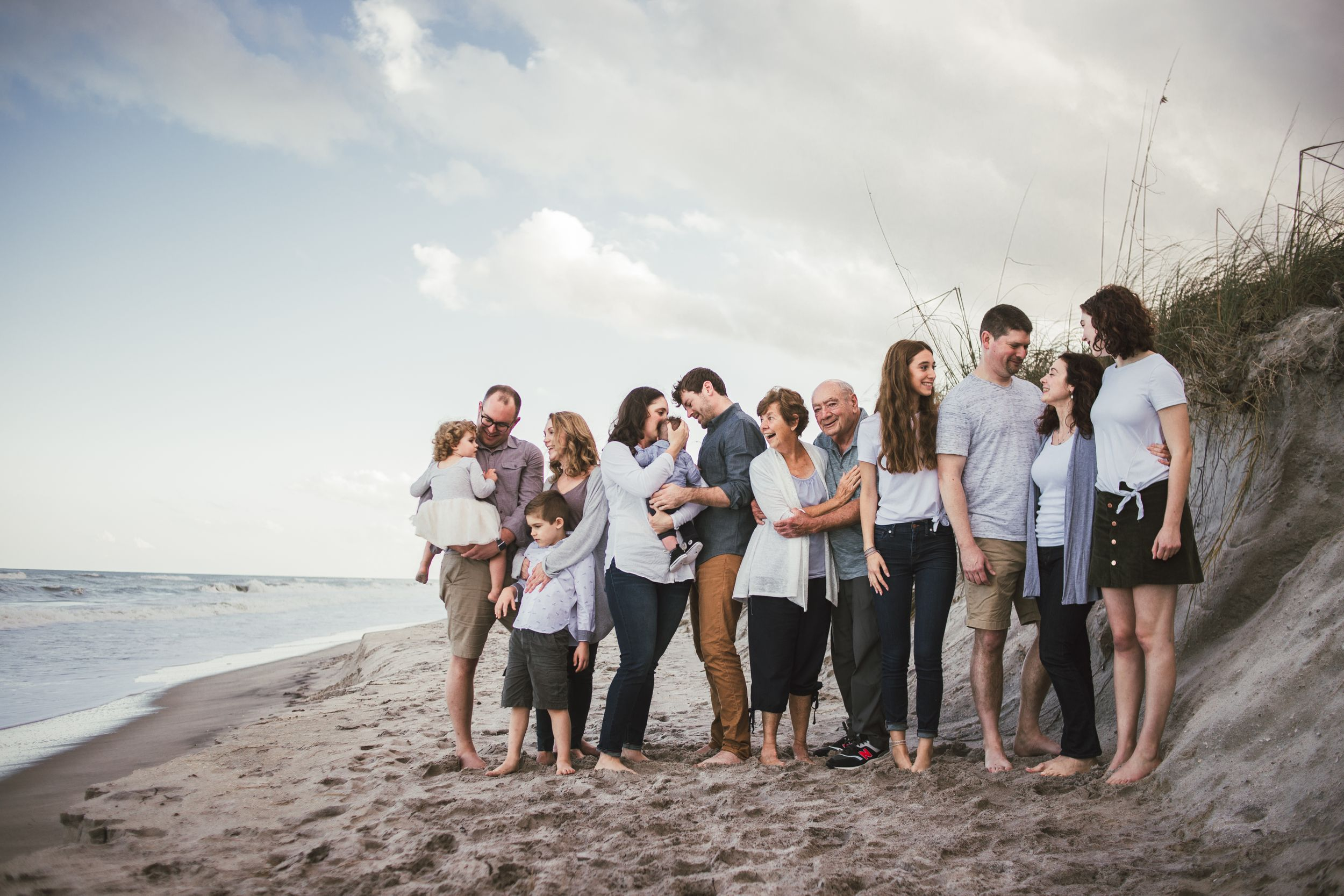 An extended family on the beach at sunset. Grandparents are surrounded by their family. Ages two months to 80 years.