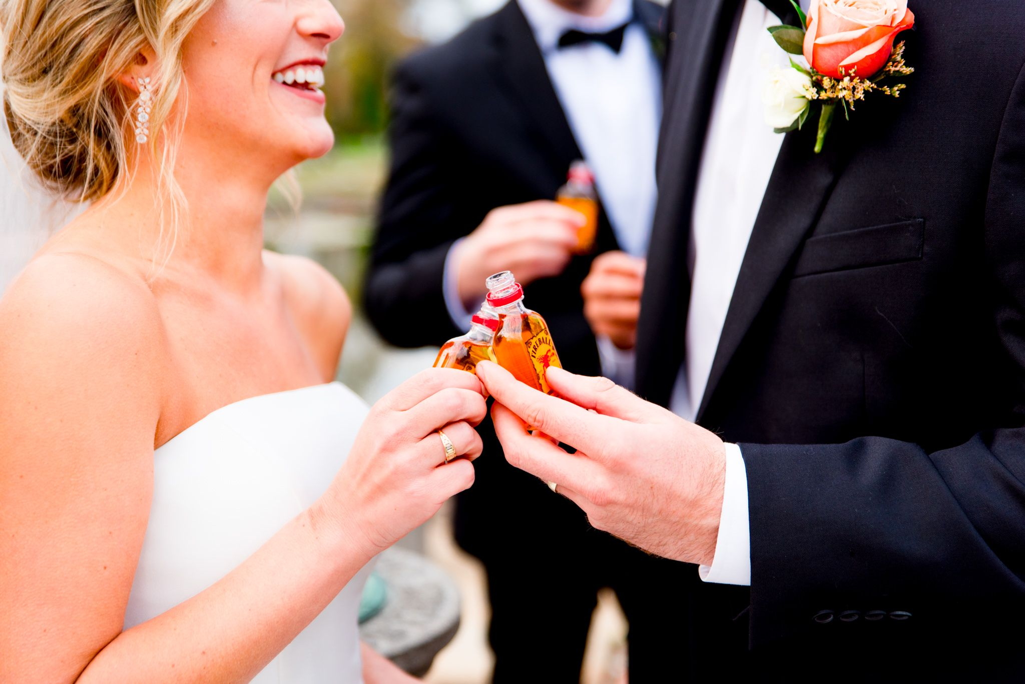 bride and groom clinking shot bottles of Fireball