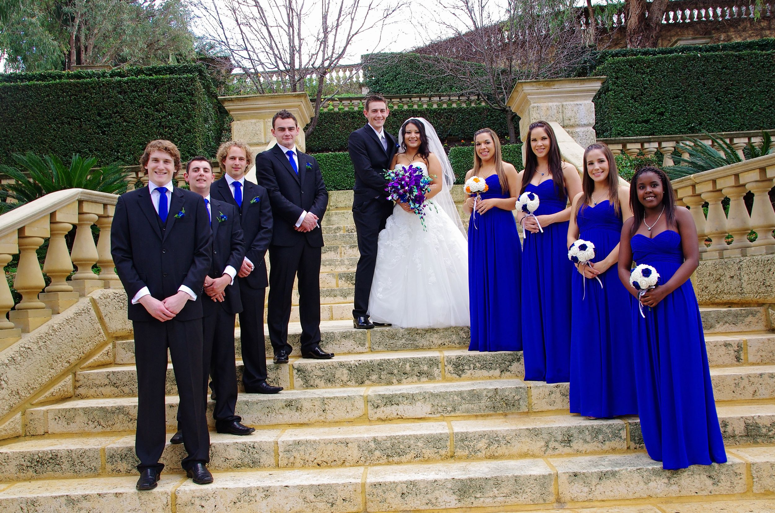 bridal party posing on steps and looking at camera with bride and groom