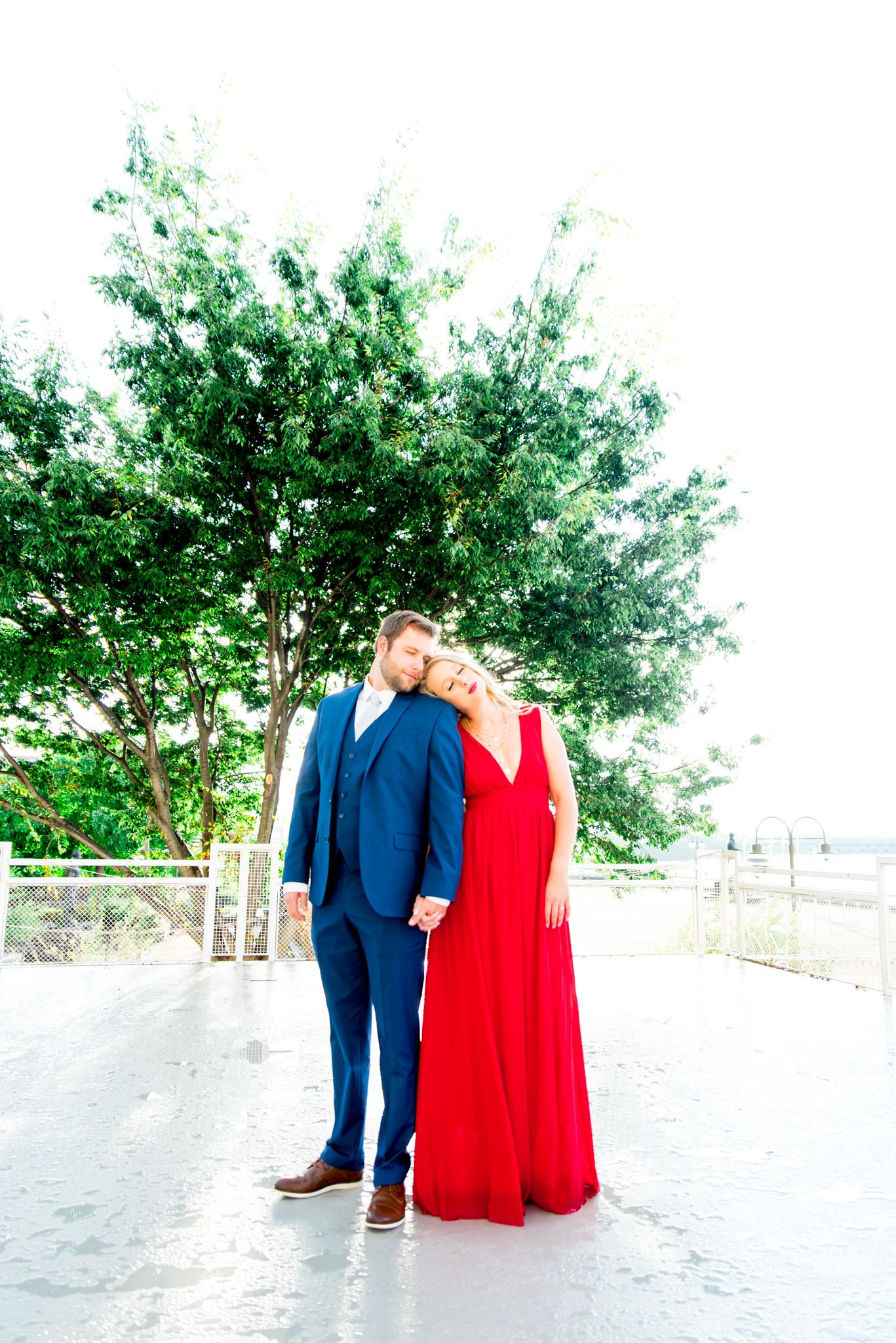 blonde woman in red dress and man in navy suit lean on each other with eyes closed in front of big tree