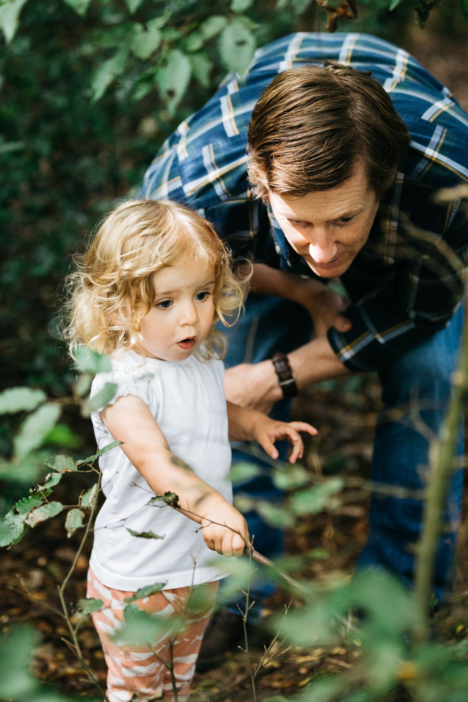 surprised toddler girl with blonde curly hair showing dad forest