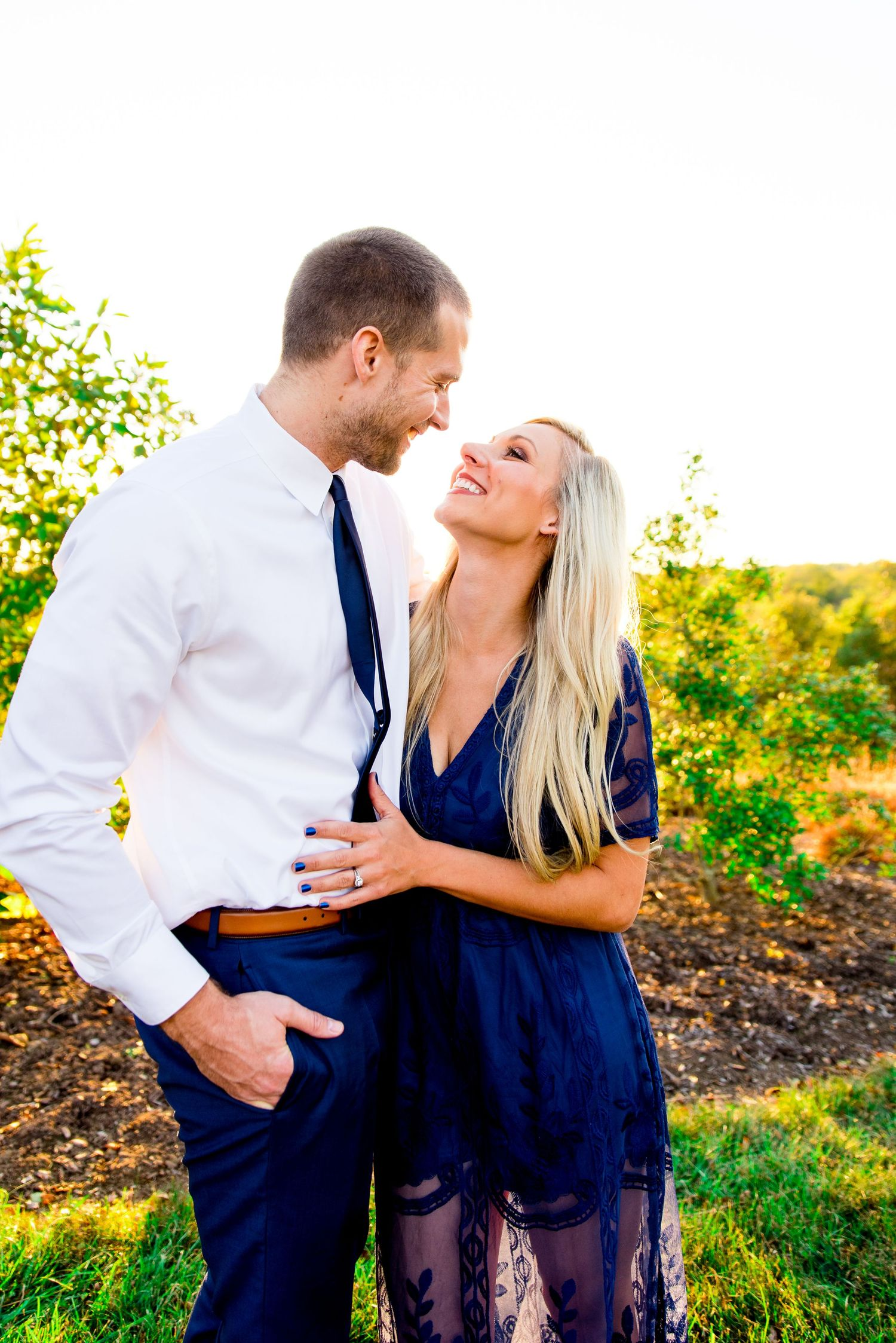 woman with long blonde hair in navy dress smiles at husband in white shirt and navy pants and tie