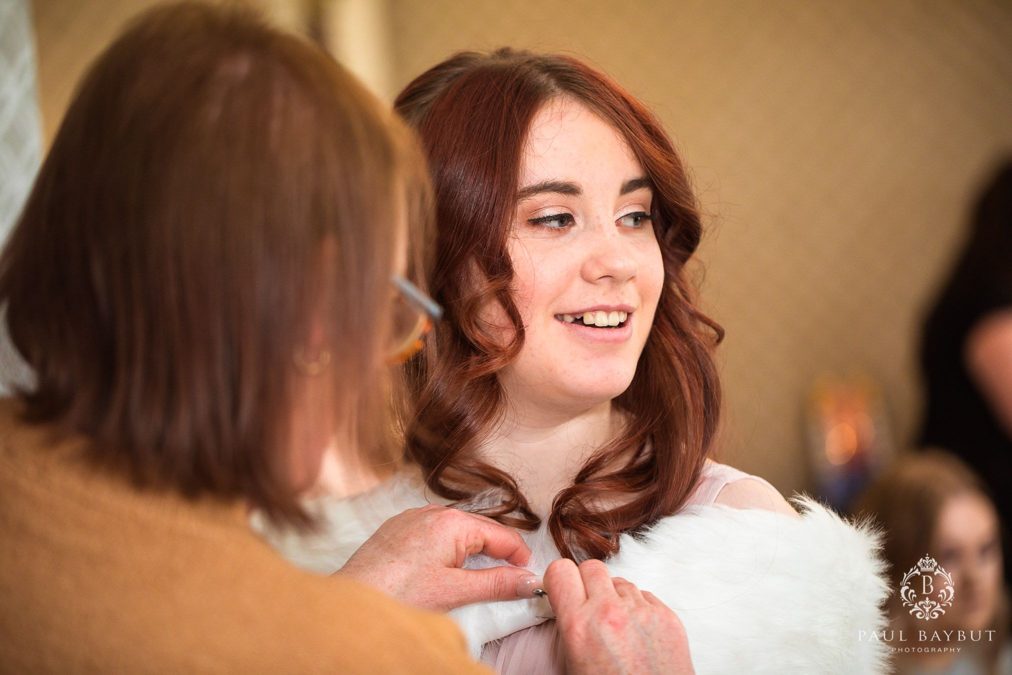 Mottram Hall wedding blog photography of red haired bridesmaid getting ready with help from her Mother