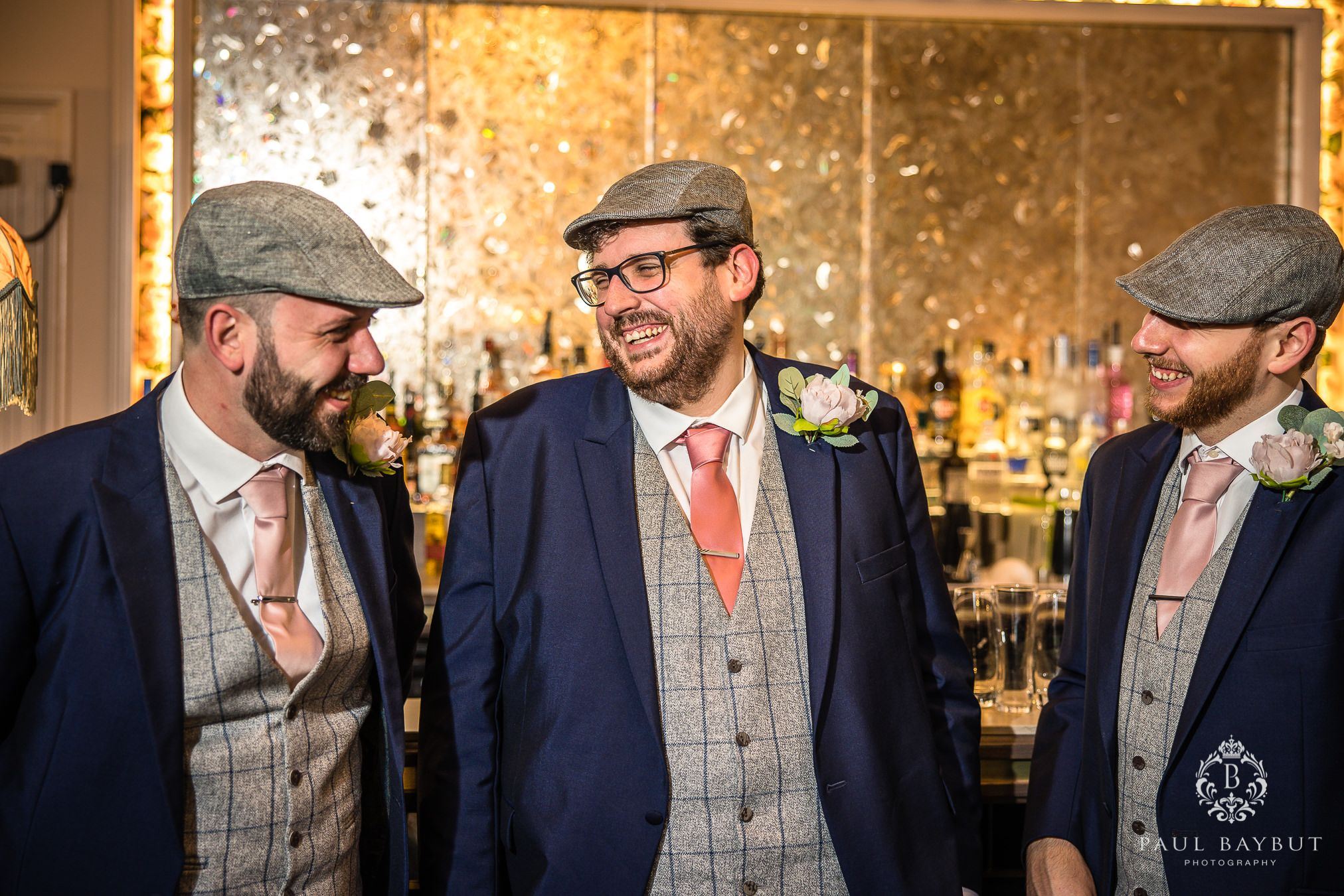 Laughing, happy groom and groomsmen at Mottram Hall pose for a photo by Manchester wedding photographer Paul Baybut