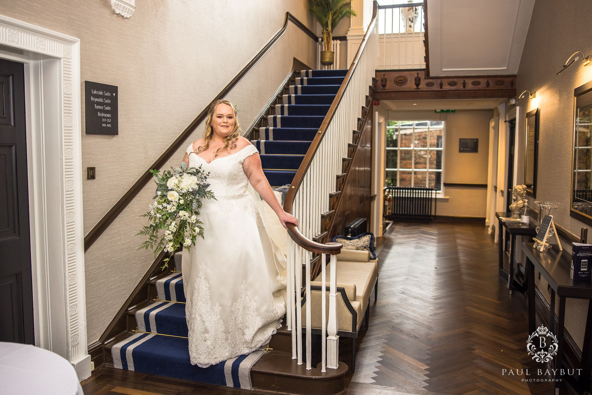 Cheshire bride in white dress on the staircase at Mottram Hall wedding venue