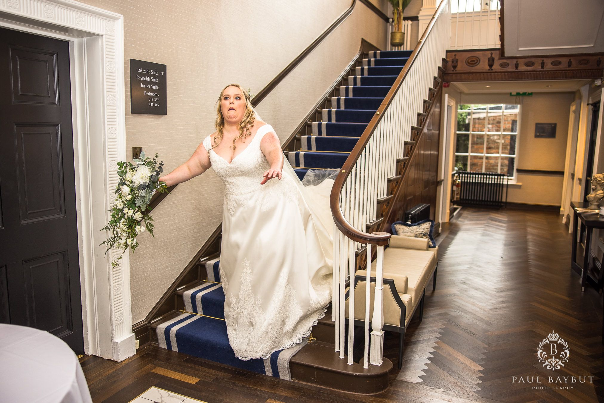 Cheshire bride mock falls on the staircase at Mottram Hall wedding venue