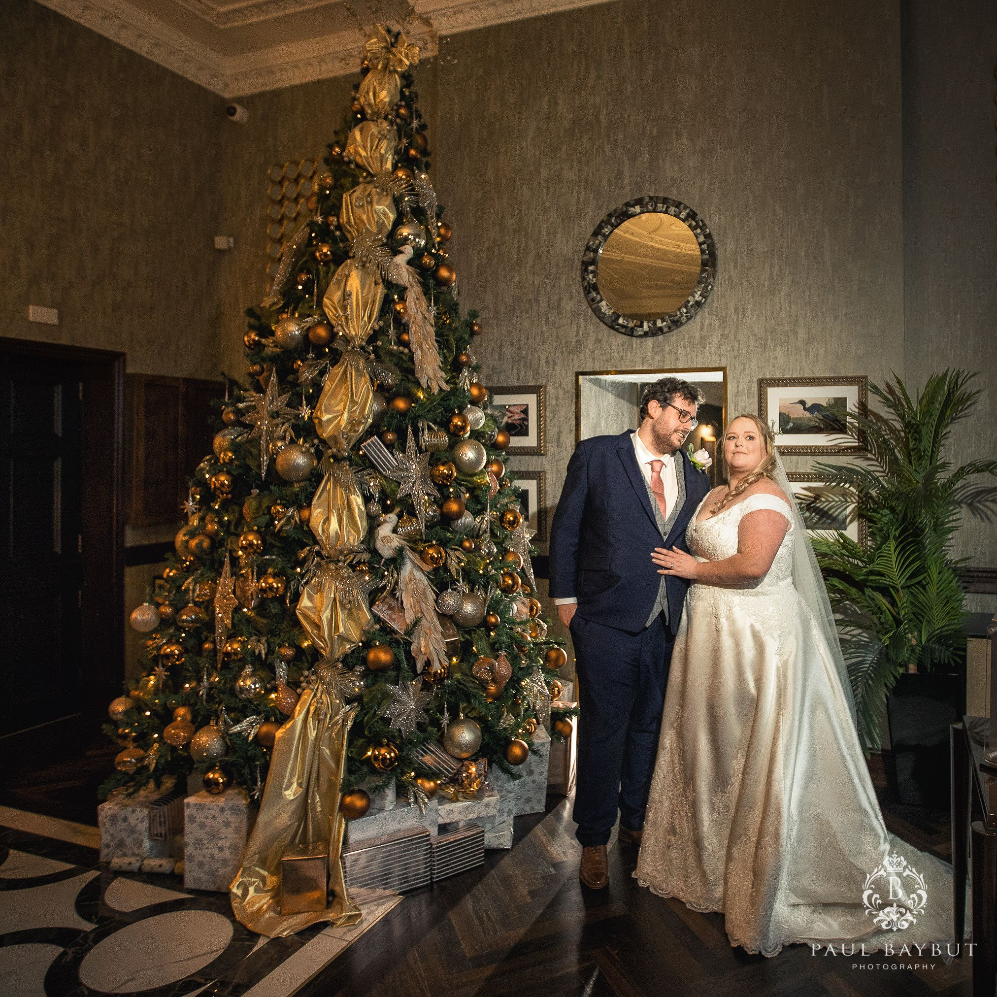 Mottram hall wedding photographer Christmas micro wedding with bride and groom at the Festive tree in reception area