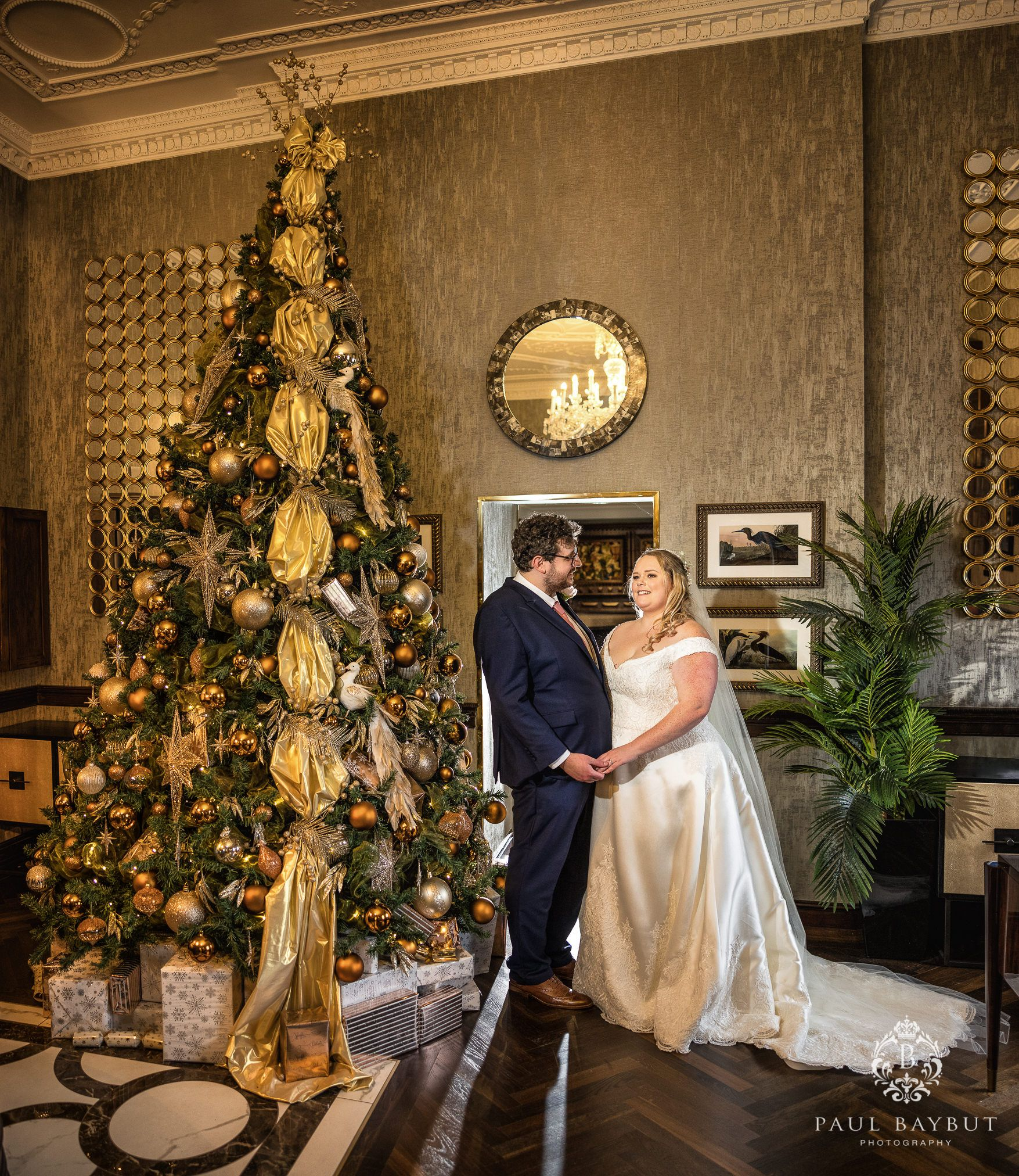 Christmas wedding at Mottram Hall with bride and groom standing by the Christmas tree in reception