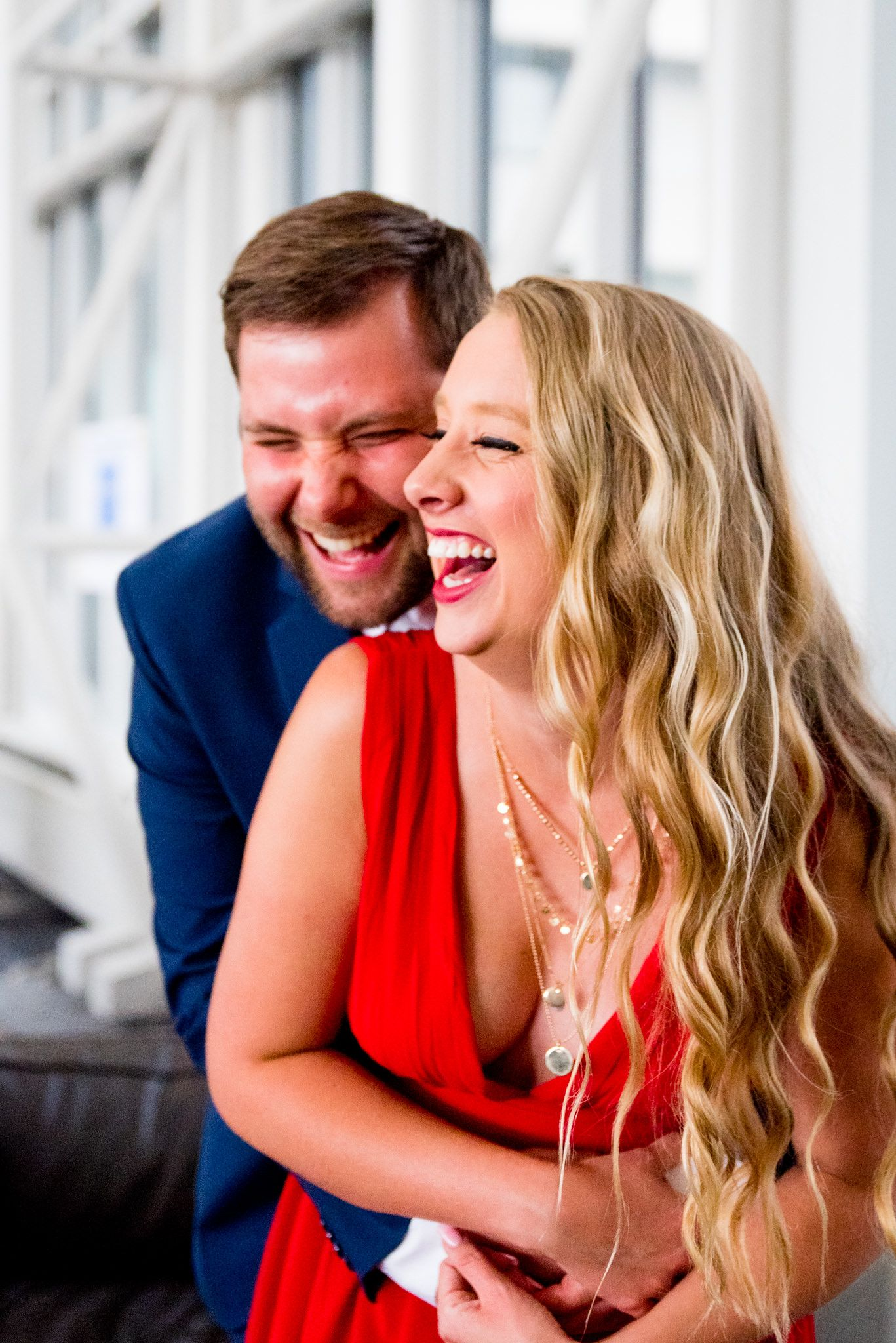 blonde woman in red dress laughing with fiance in navy suit at Galt House Hotel engagement pictures