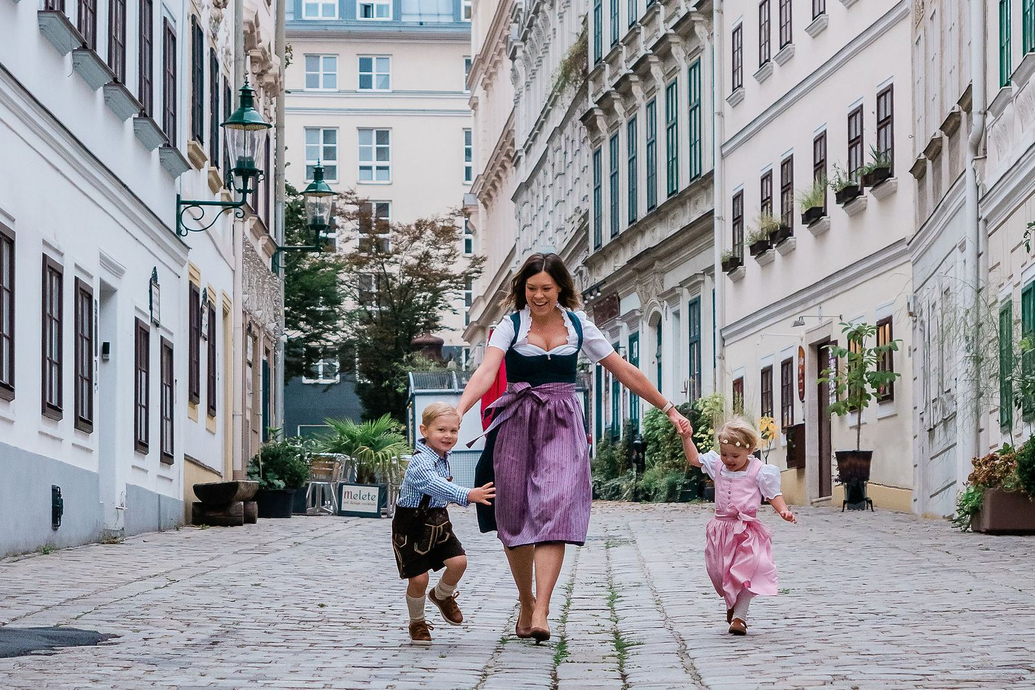 Mother running with kids in Spittelberggasse  7th district  Vienna wearing traditional outfit